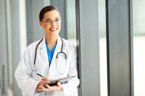beautiful female healthcare worker writing report in office