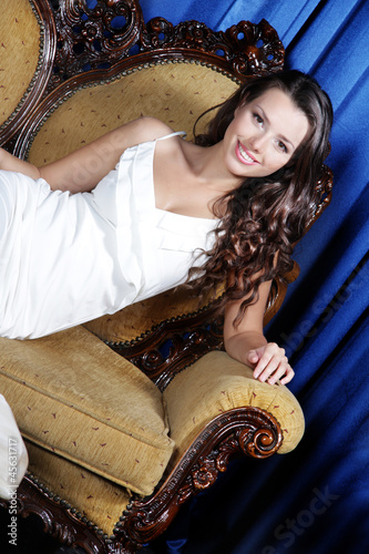 young beautiful elegant woman sitting in armchair