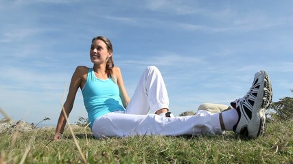 Woman in fitness outfit relaxing outside in countryside