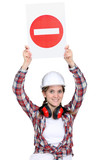 Female manual worker holding warning sign