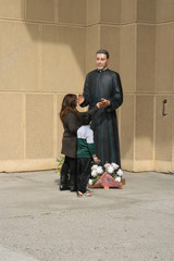 Madre e hijo junto a la estatua de un santo