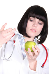 Doctor injecting an apple