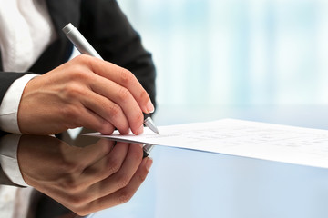 Extreme close up of female hand signing document.