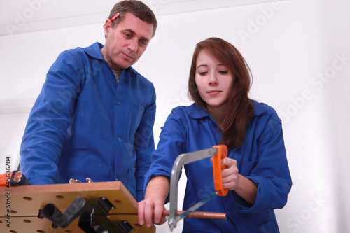 craftsman and apprentice cutting a pipe