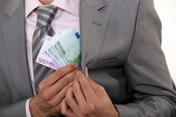 Businessman pulling money out of pocket