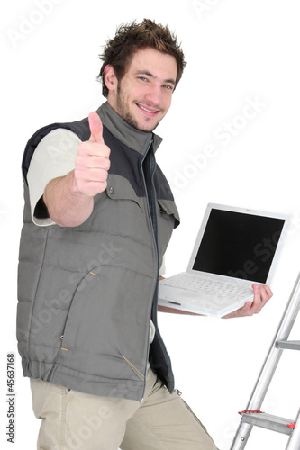 Tradesman posing with his tools and giving the thumb's up