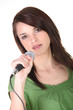 Girl singing into microphone on white background