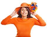 Woman wearing orange sweater and hat.