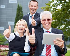 Lachendes Business-Team hält Daumen hoch