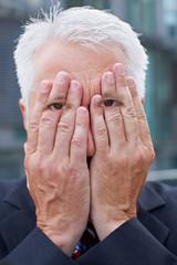 Älterer Manager mit Händen auf den Augen
