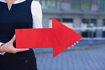Frau hält roten Pfeil