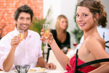 Man and woman holding champagne glasses in restaurant