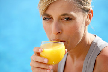 Woman enjoying refreshing orange juice by the pool