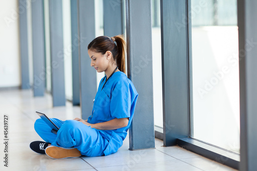 pretty nurse sitting on floor and using laptop computer
