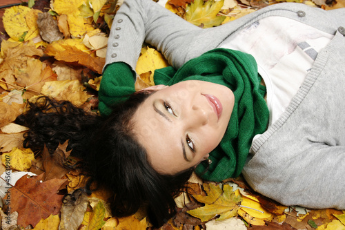 Woman lying on the leaves in the park