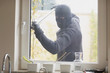 Burglar breaking a kitchen window