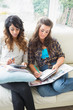 Two friends sitting on couch doing homework