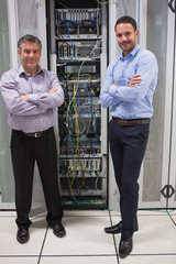 Two technicians standing in front of servers