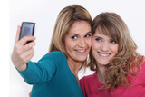 Two girls taking a picture with a mobile phone