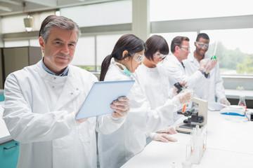 Smiling chemist using tablet pc