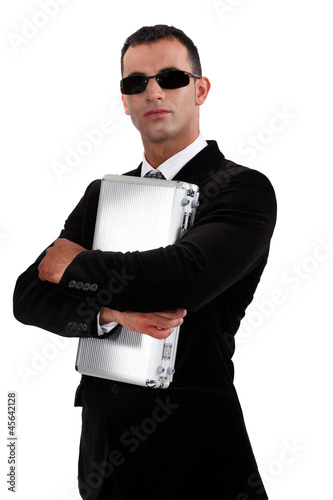 Man in sunglasses protecting briefcase