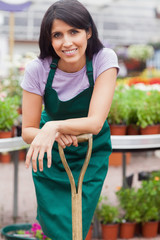 Woman leaning on shovel in garden center