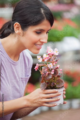 Woman holding a flower and smelling