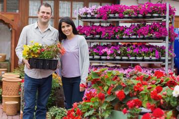 Happy couple holding tray of plants