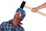 Injured tradesman being hit over the head with a mallet poster