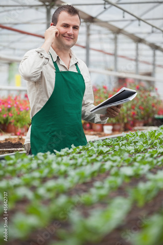 Smiling man on the phone and taking notes in greenhouse