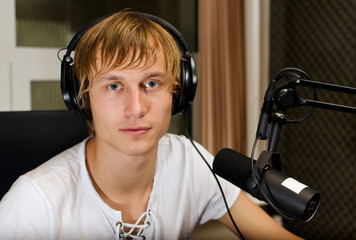 Male dj working in front of a microphone on the radio