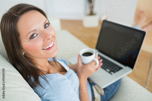 Woman drinking a coffee and using her laptop