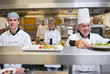 Smiling chef putting salad on order station