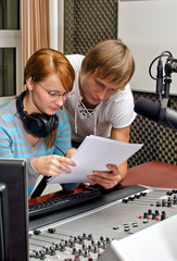 Colleagues examine broadcast list in studio