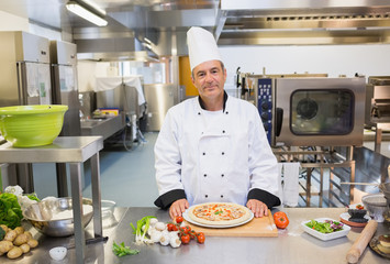 Chef standing in the kitchen with pizza
