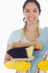 Smiling woman holding cleaning tools