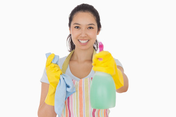Cheerful woman holding up spray bottle