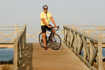 Mature man sitting on his bike over a wooden bridge