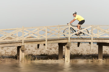 Mature male riding a bicycle over a bridge