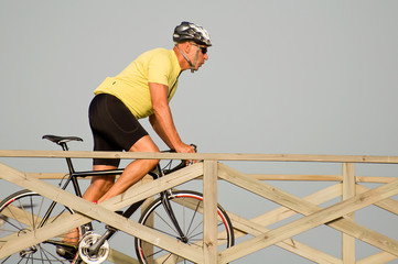 Mature man riding a bicycle over a wooden bridge