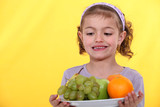 Little girl holding plate of fruit