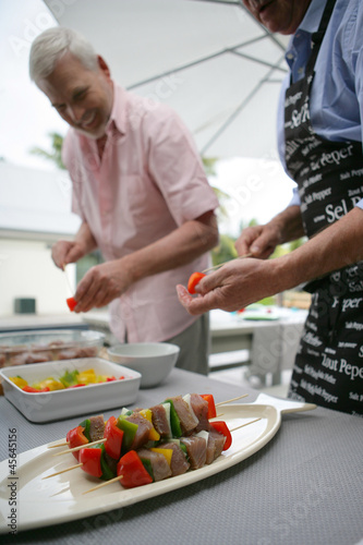 two men making skewers