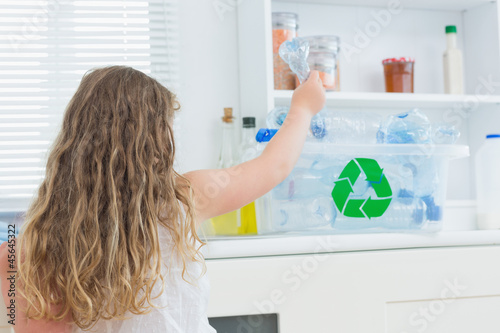 Girl putting bottle in recycling box
