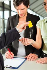 Car sales - dealer handing woman auto key