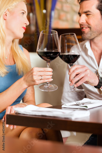 Attractive couple drinking red wine in restaurant or bar
