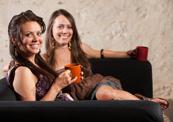 Two Grinning Ladies Sitting on Sofa