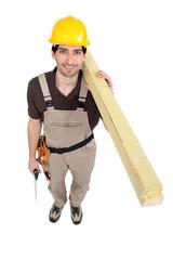 Man carrying planks over shoulder