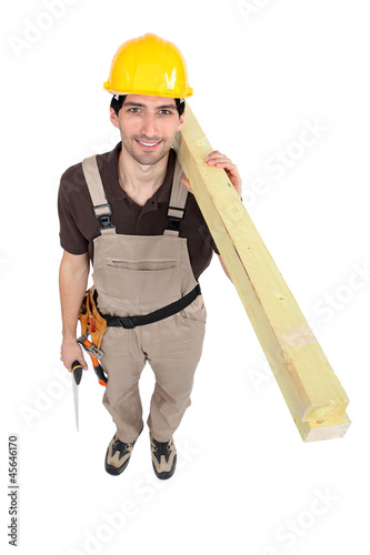 Man carrying planks over shoulder