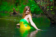 Blond young woman standing waist water in the river in green for