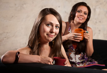 Smiling Ladies on Sofa with Mugs